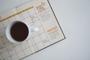 Birdseye view of a managers bullet journal open on calendar page and a  cup of coffee sitting on top.