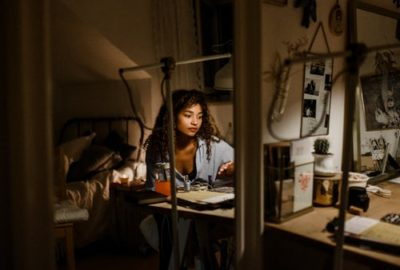 Woman sitting at her bedroom desk working on her side-hustle late at night