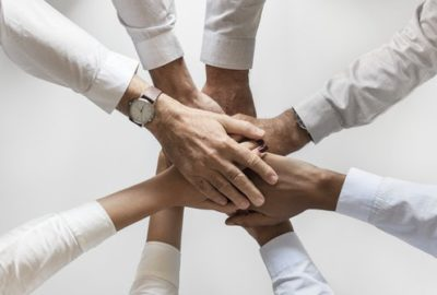 Team members holding hands as signal to employers that they are working well together